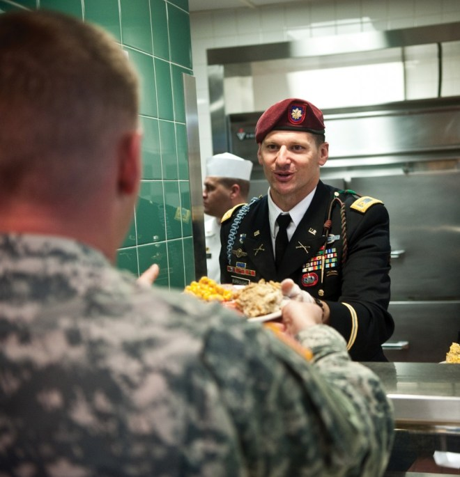 Fort Bragg holds its annual Thanksgiving meal on Wednesday. Officers, such as Maj. Jeff Burroughs, go behind the counter to pile fixings high atop the troops' plates.