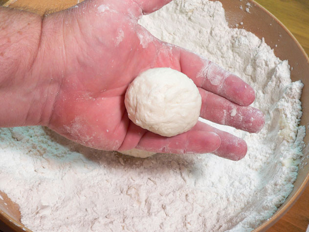 You should end up with a round ball of dough like this. Notice it's pretty smooth on the outside at this point. Rolling it around in your hands should smooth out any splits or folds in the dough. If it has places like that, roll it around a little more. Use a light touch and don't press the dough together very hard.