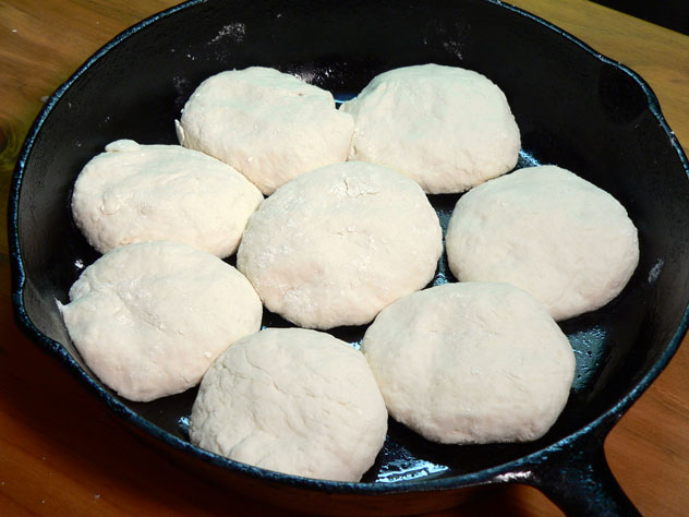You will need to lightly grease your baking pan with a little lard or butter. You can use a flat baking sheet or a cast iron skillet.  Just keep repeating the process of shaping the biscuits until you've filled the pan or run out of dough. I prefer to have the sides touching as it makes the edges softer.  If you space the biscuits an inch or so apart on a baking sheet, they will have more of a crust around the edges as they bake up. It's a personal choice, but try it both ways and see which you like best. I opted to bake these in one of mama's old cast iron skillets. It is of course my favorite and most treasured kitchen item.  When mama baked biscuits for Sunday dinner, she made about two dozen or more biscuits at a time.  She would bake those on large baking sheets instead of the skillet. I thought you'd like to see them in the skillet though.
