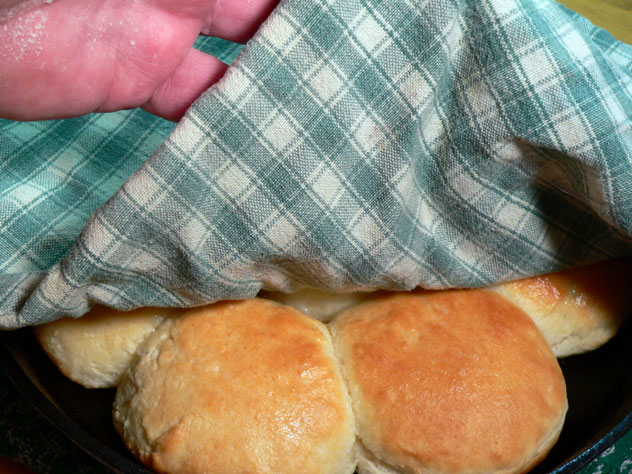 Cover the hot buttered biscuits with a clean towel and let them rest for a few minutes, or until you're ready to serve them.