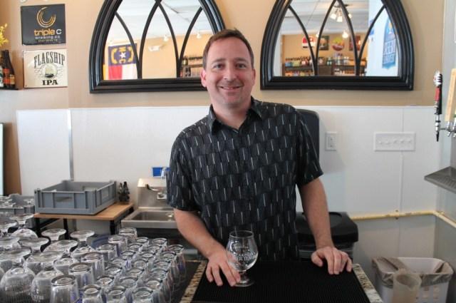 Rob Jacik stands behind the bar of the Carolina Beer Temple.