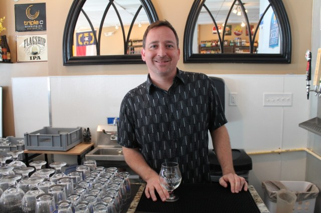 Rob Jacik stands behind the bar of the Carolina Beer Temple.