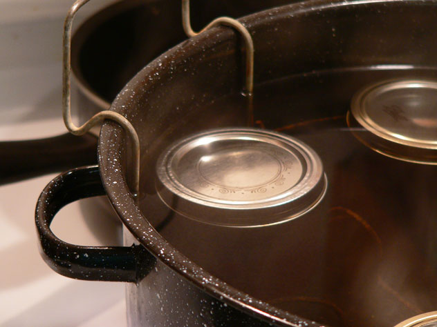 """When the proper amount of time has gone by, raise the rack back up and hook it back on the rim of the canning pot. The jars need to just sit here for about 5 minutes before you remove them. I always use tongs to raise the rack. Just remember that water is HOT, so be careful. Again, if a jar tilts over, just sit it back up straight. You might even hear a jar """"ping"""" as it seals during this time."""
