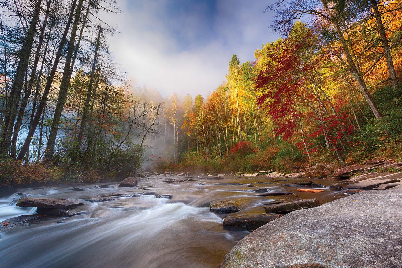 A misty autumn morning at High Falls in Transylvania County, where the Little River nears a 125-foot drop. Photograph by Brendan Arcuri, dezignhorizon.com