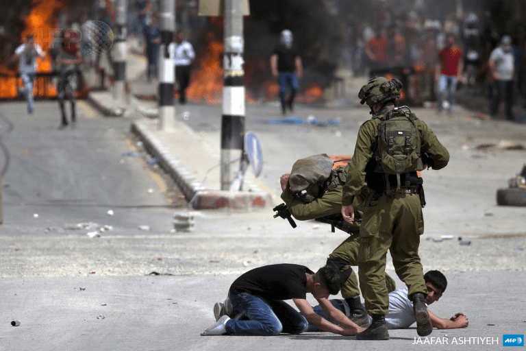 Israeli soldiers arrest Palestinian demonstrators amid clashes in the West Bank village of Beita, southeast of Nablus city, on April 21. (Photo: APF / Jaafar Ashtiyeh)