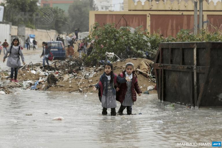 Palestinian school girls walk in a flooded street during heavy rain in Gaza City on November 21, 2017. (Photo: AFP / Mahmud Hams)