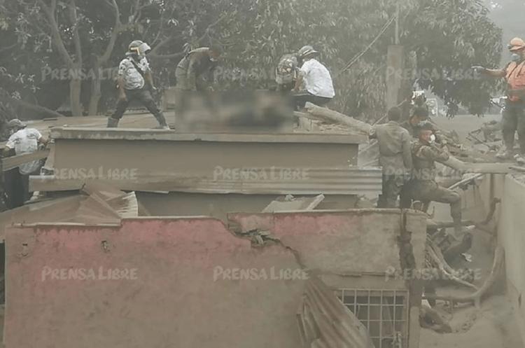 Socorristas sacan por el techo el cuerpo sin vida de un hombre en Los Lotes, Escuintla. (Foto Prensa Libre: Enrique Paredes)