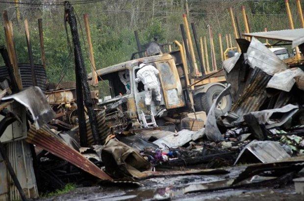 Agentes de policía investigan el lugar donde fueron quemados 29 camiones. (EFE).