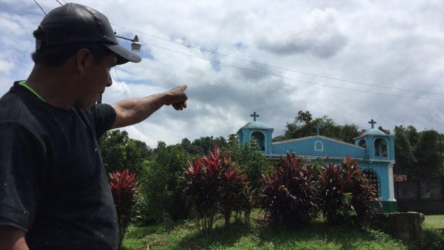 Benjamín Sarat señala al volcán, oculto entre las nubes detrás de la iglesia de El Viejo Palmar. BBC NEWS MUNDO