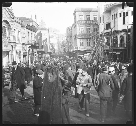 A crowd in Constantinople walking through a busy narrow street lined by buildings that are 2 and 3 stories tall. A woman in the foreground has her face covered by a sheer black veil.