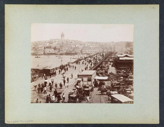 A scene of people walking across a bridge in a busy city.