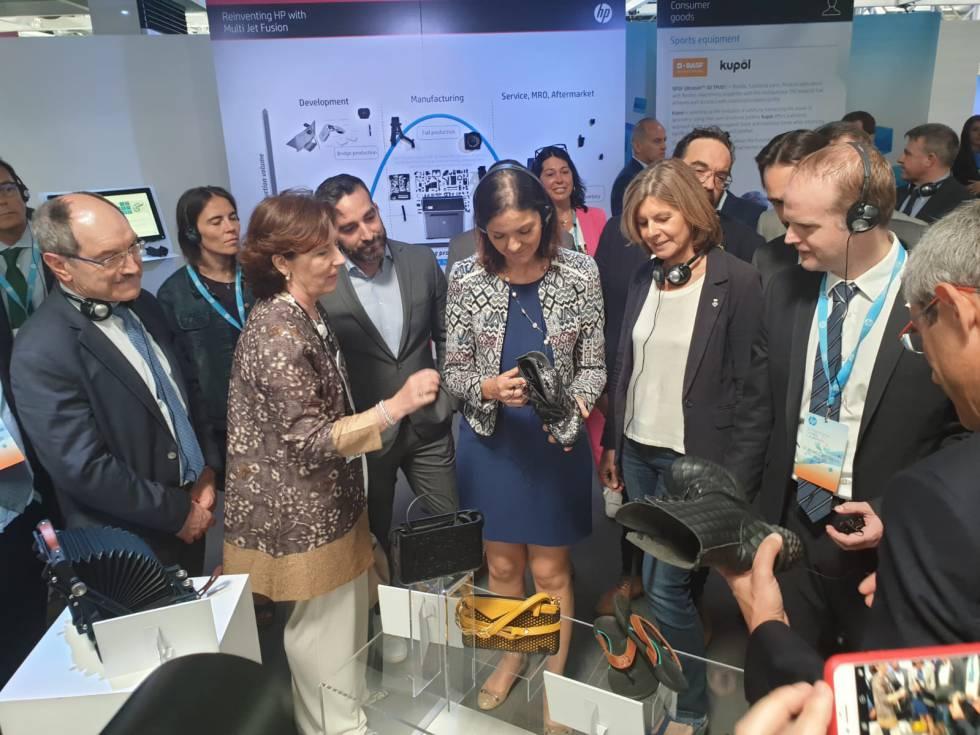 Helena Herrero, presidenta de HP Iberia muestra a la ministra de Industria, Comercio y Turismo, Reyes Maroto, una bota que tiene el tacón hecho con impresión 3D.