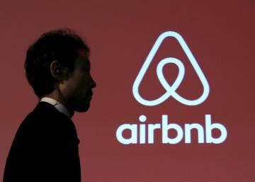 Un hombre pasa delante del logo de Airbnb en una conferencia en Tokio.
