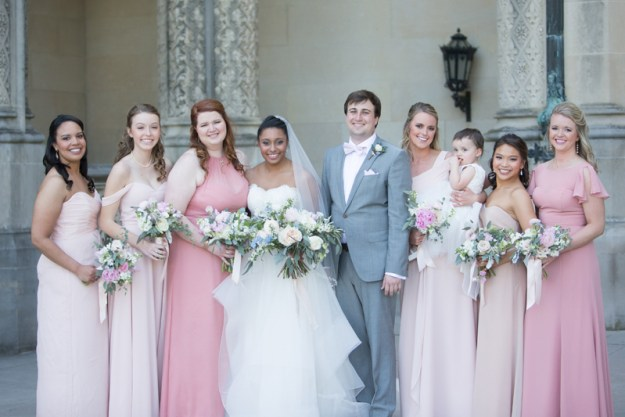 Bride with bridesmaids dressed in various shades of pink
