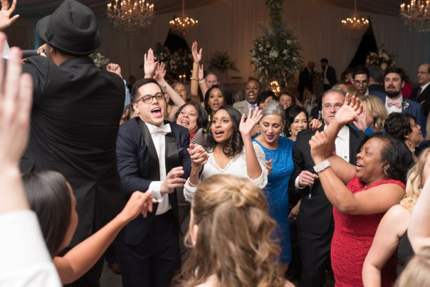 Bride, groom and their guests dance to Sol Fusion band at wedding reception.