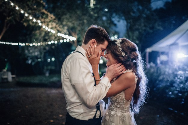 bride and groom embracing with string lights in background