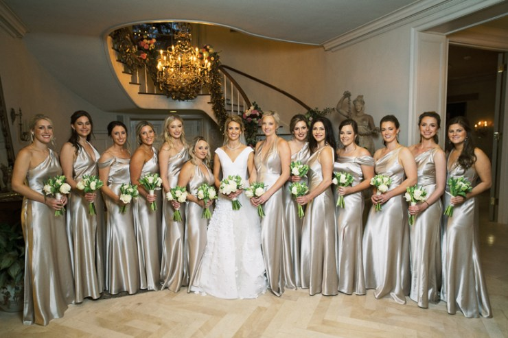 Bride surrounded by large bridal party in gold dresses