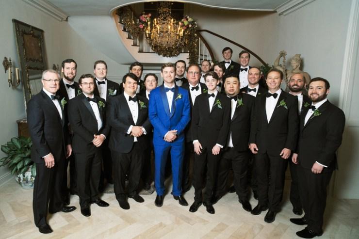 Groom in blue suit surrounded by groomsmen