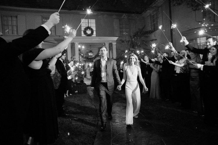 Bride and groom exiting wedding reception to sparklers.