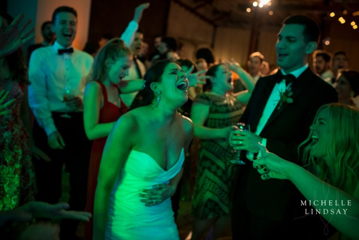 Bride laughing and signing on dance floor with Modern Luxe band.