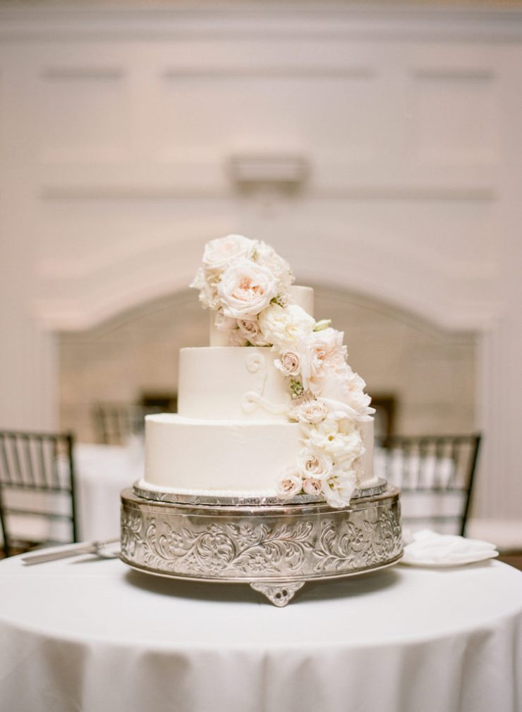 Three tiered wedding cake with cascading flowers.