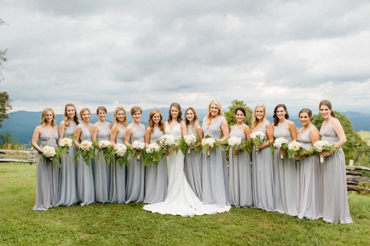 Bride and bridesmaids posing in a line at Roaring Gap Club wedding.