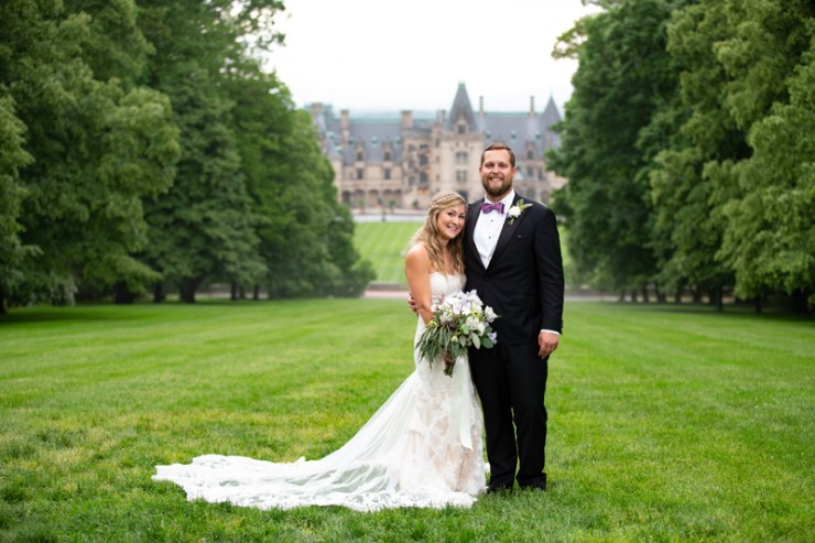 Bride and groom posing in front of Biltmore Estate.