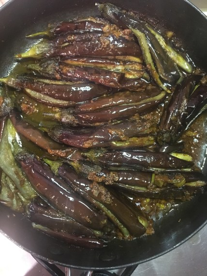 In go the fried aubergines. Add water.