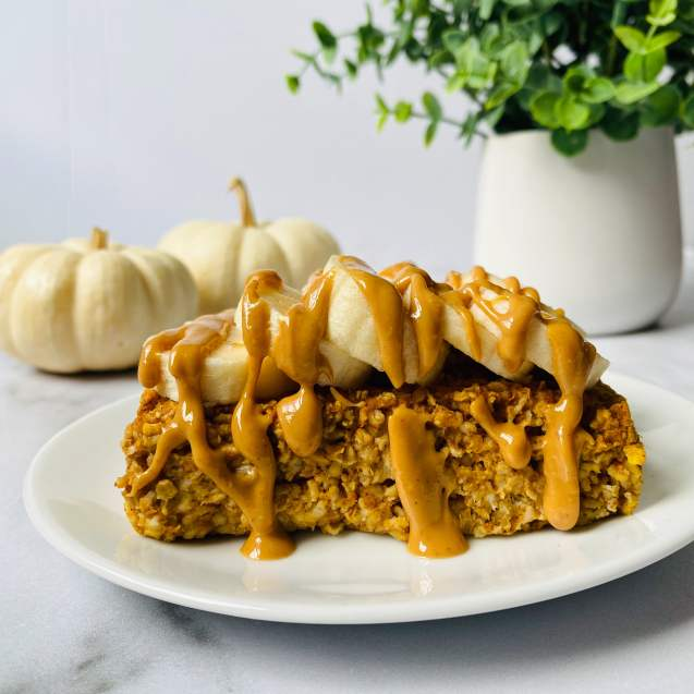 Close up of pumpkin spice baked oatmeal topped with banana and peanut butter and white pumpkins in the back left and a green plant in the back right against an all white background.