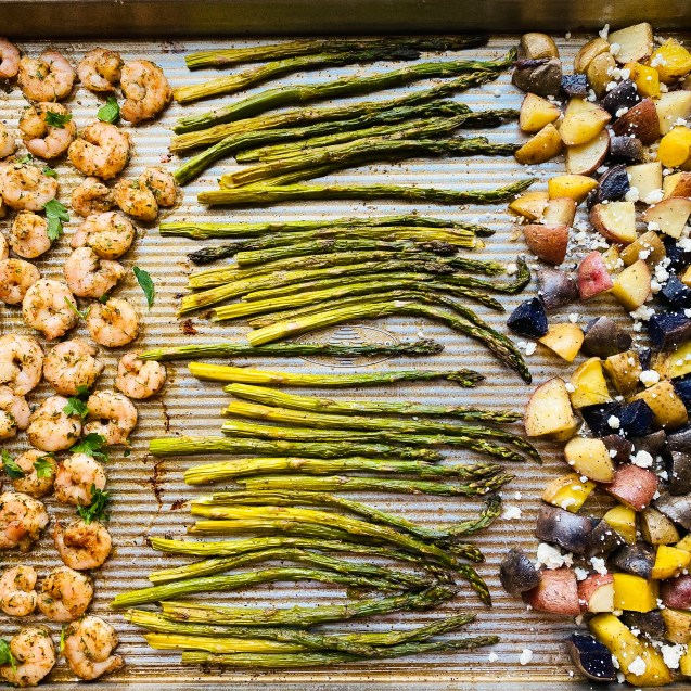 Close up of greek shrimp sheet pan on the sheet pan. From left to right: greek shrimp, asparagus, and mixed color potatoes with feta.
