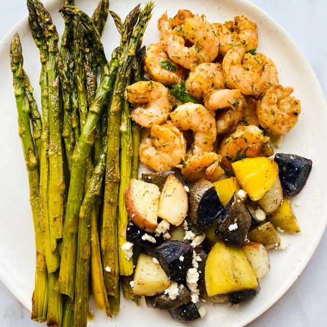 Close up of greek shrimp sheet pan meal of asparagus, shrimp, and mixed color potatoes with feta on a white plate and white background.