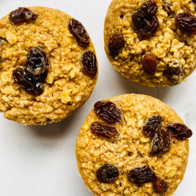 Overhead close up shot of three cinnamon raisin baked oatmeal cups against a white background.