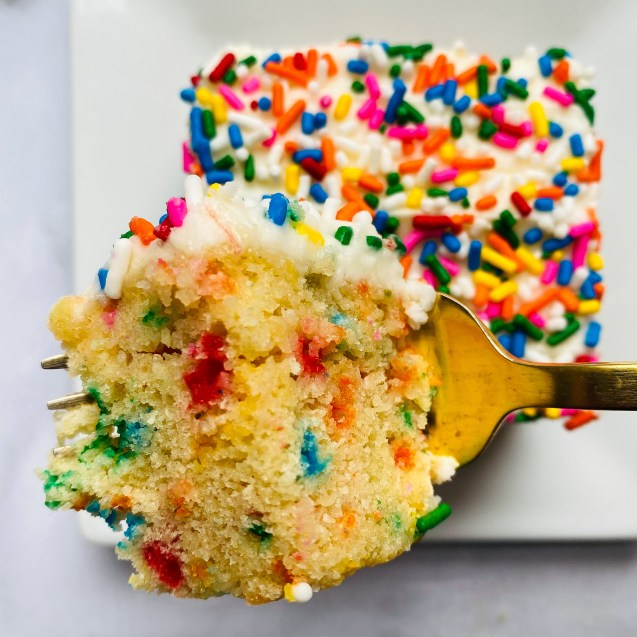 Close up shot of a bite of funfetti snack cake on a gold fork with a square slice of cake in the background on a white marble background.