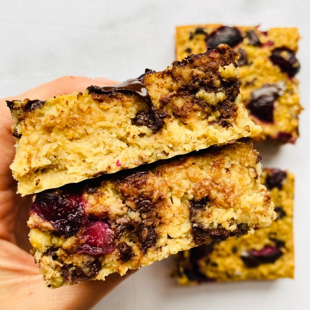 Close up shot of two chocolate cherry baked oatmeal squares stacked on top of each other with a hand holding them against white background.
