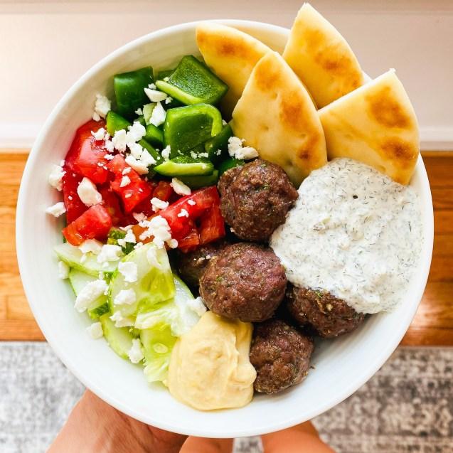 White bowl filled with greek meatballs, cucumber, tomato, bell pepper, feta, hummus, tzatziki, pita bread against a floor.
