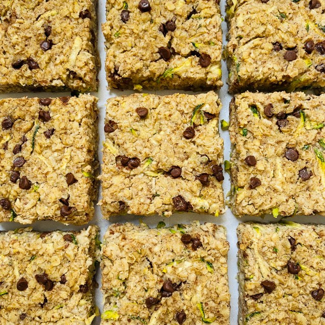 Photo of very close up of 9 squares of chocolate chip zucchini baked oatmeal on a white background.