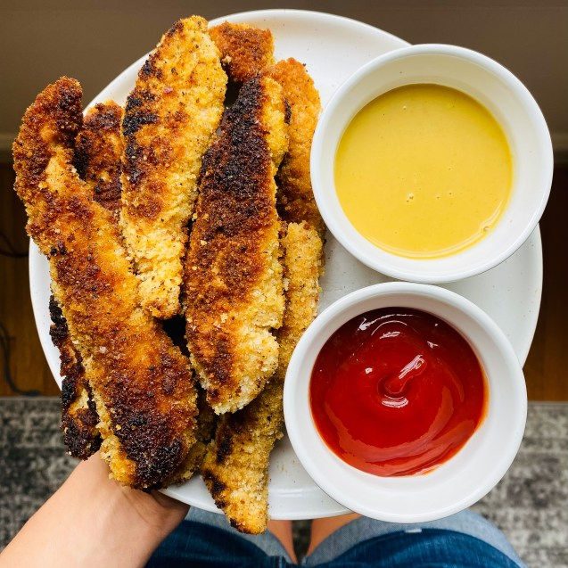 Overview of hand holding a white plate filled with crispy chicken tenders on the left and honey mustard and ketchup on the right.