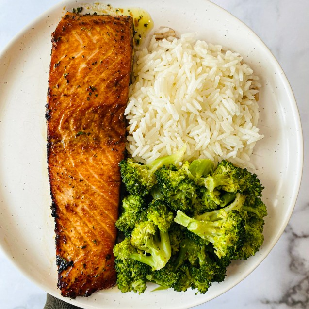The best soy glazed salmon on a white plate paired with white rice and broccoli against a white background.