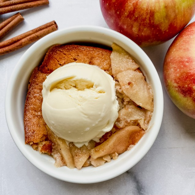 A scoop of the easiest apple cobbler in a white circle serving bowl topped with a scoop of vanilla ice cream and two apples in the top right corner and cinnamon sticks in the top left corner.