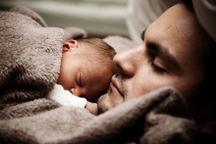 A stay at home dad laying with newborn baby