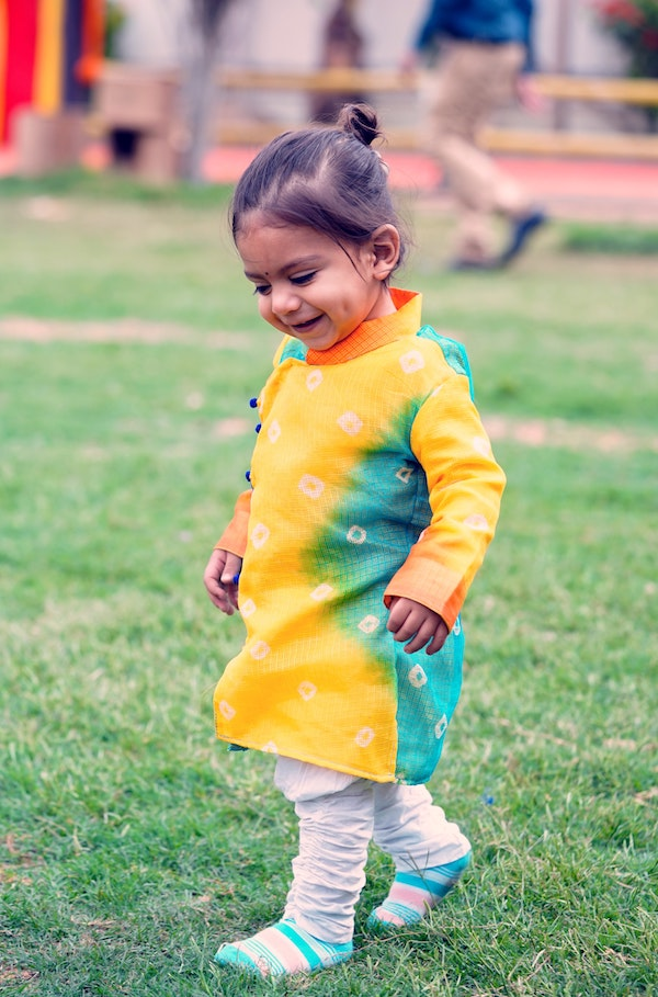 A toddler girl walking in a park