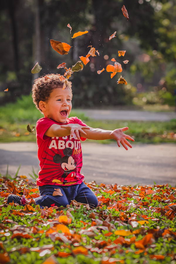 Boy in grass throwing leaves