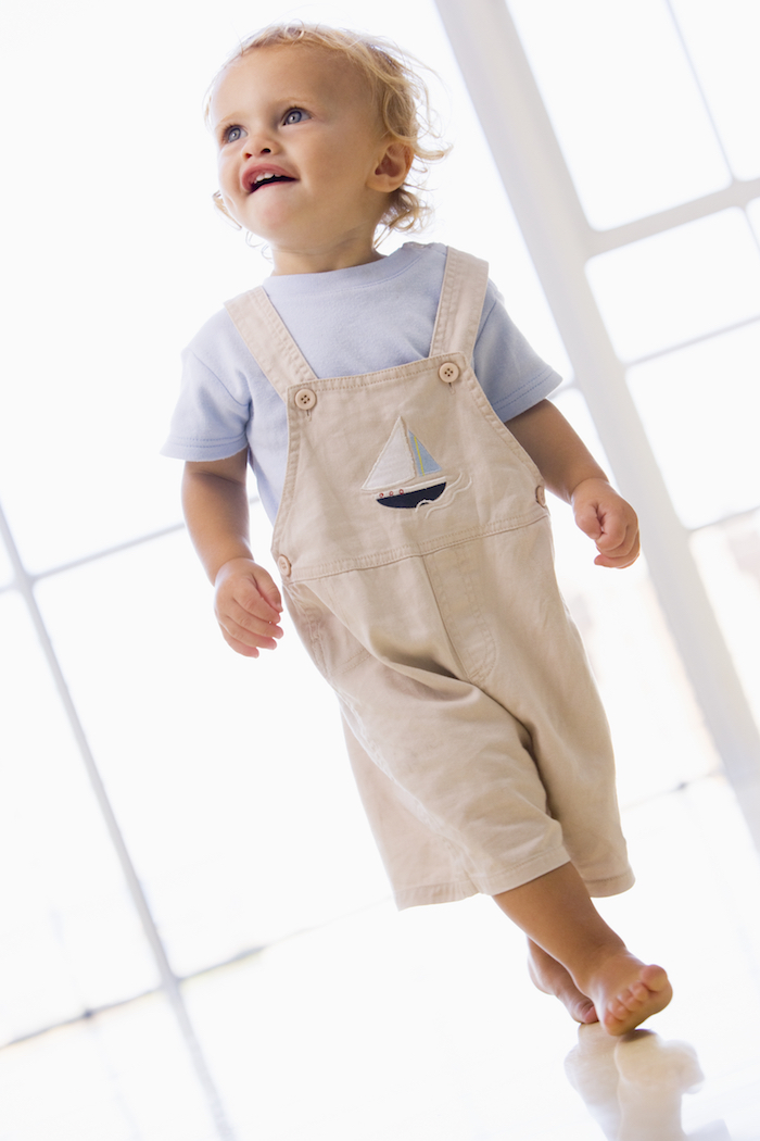 Boy walking in overalls inside
