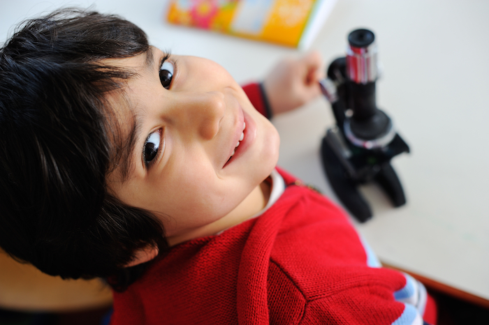 Boy playing with microscope and smiling
