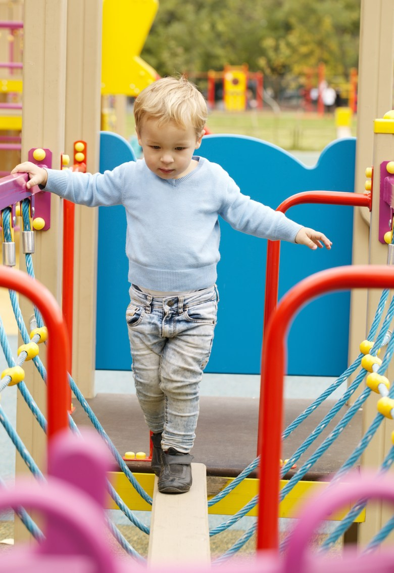 Cute little boy playing in a playground carefully balancing on a plank suspended by ropes with colourful guide rails to hold onto