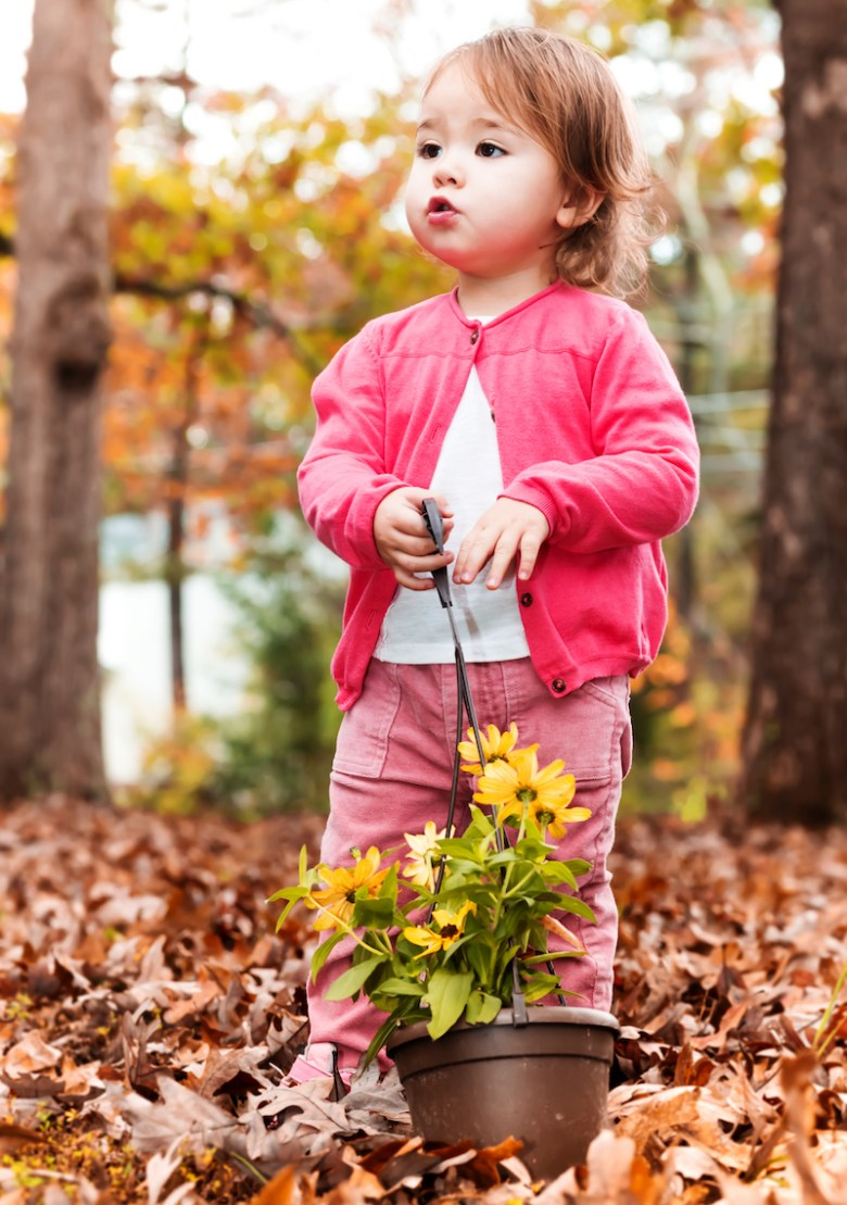 Happy toddler girl happily playing outside with flower pots in autumn