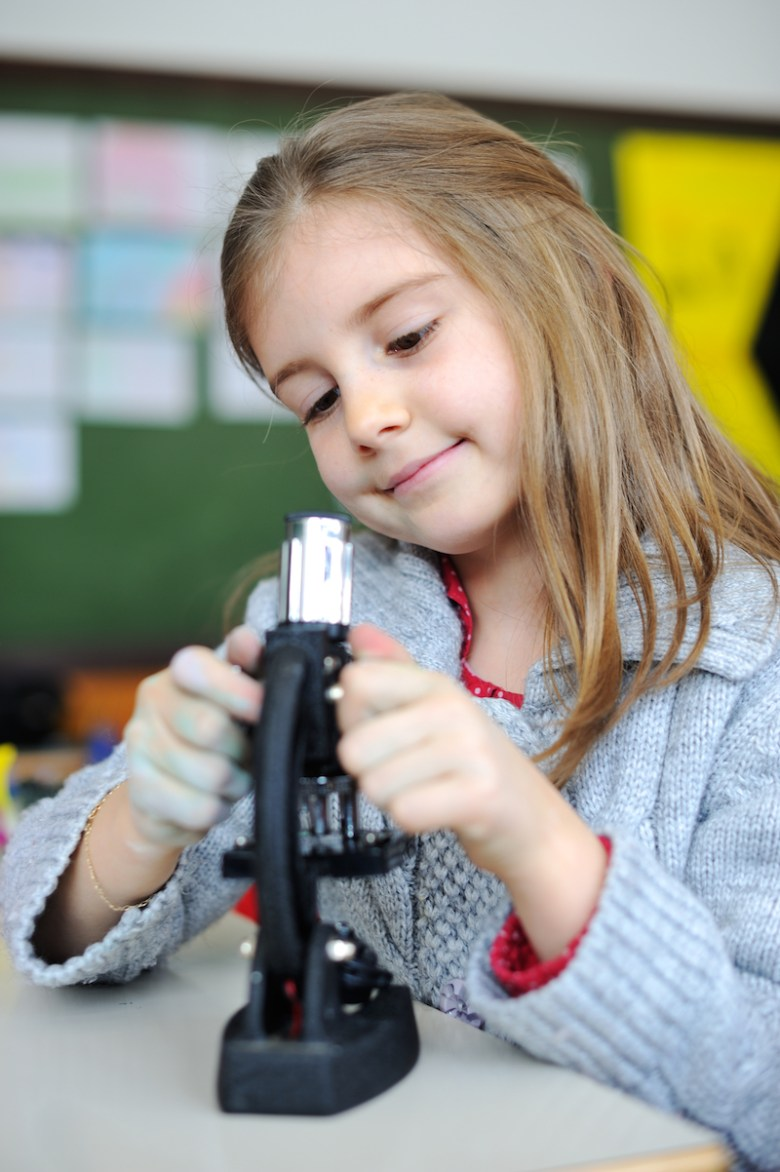 Young girl named Paisley looking through microscope