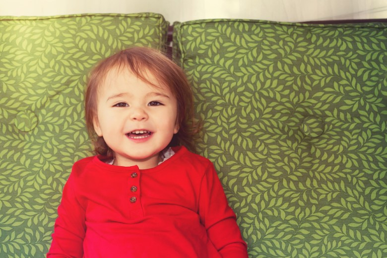 Toddler girl named Natalie smiling on couch