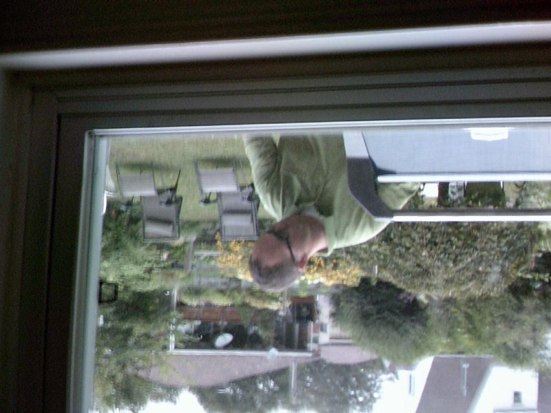 Upside down image of man outside window cooking at barbeque