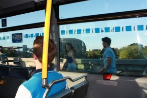 Image of people walking past a bus from the inside of the bus